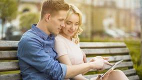 Étudiants dans l'amour se reposant sur le banc, utilisant l'ordinateur portable, choisissant où passer l'été Photographie stock libre de droits