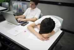 Étudiants dans l'apprentissage en ligne et le sommeil uniformes Photos stock