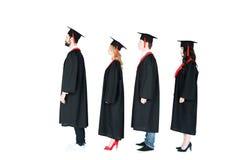 Étudiants dans les chapeaux scolaires et des robes d'obtention du diplôme se tenant dans une rangée Photo libre de droits