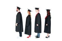 Étudiants dans les chapeaux scolaires et des robes d'obtention du diplôme se tenant dans une rangée Photo stock