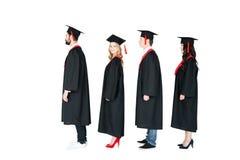 Étudiants dans les chapeaux scolaires et des robes d'obtention du diplôme se tenant dans une rangée Image stock