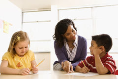 Étudiants de aide de professeur avec Schoolwork Images libres de droits