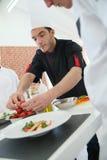 Étudiants de formation de chef dans le cours de cuisine Image stock