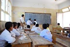 2 étudiants de garçons dans l'écriture de salle de classe sur le tableau noir Image libre de droits