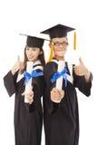 Étudiants de graduation heureux avec le pouce  Images stock