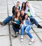 Étudiants de groupe s'asseyant sur la rue Images stock