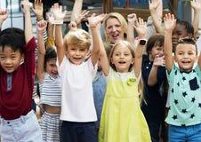 Étudiants de jardin d'enfants avec des bras augmentés Photos libres de droits