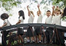Étudiants de jardin d'enfants avec des bras augmentés Photographie stock