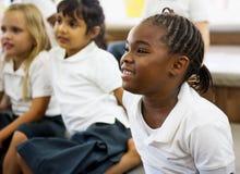 Étudiants de jardin d'enfants s'asseyant sur le plancher Photo stock