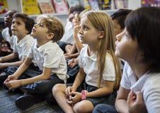 Étudiants de jardin d'enfants s'asseyant sur le plancher Image stock