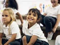 Étudiants de jardin d'enfants s'asseyant sur le plancher Images stock