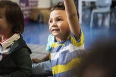 Étudiants de jardin d'enfants s'asseyant sur le plancher Images libres de droits