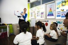 Étudiants de jardin d'enfants s'asseyant sur le plancher dans la salle de classe Photos libres de droits