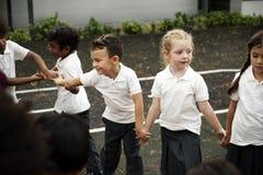 Étudiants de jardin d'enfants se tenant tenants des mains Photos stock