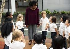 Étudiants de jardin d'enfants se tenant tenants des mains ensemble Photographie stock