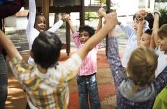 Étudiants de jardin d'enfants se tenant tenants des mains sur Photo stock