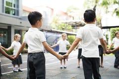 Étudiants de jardin d'enfants se tenant tenants des mains sur Photographie stock libre de droits