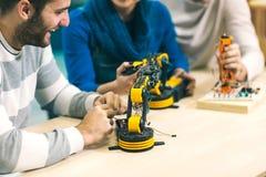 Étudiants de la robotique préparant le robot pour examiner dans l'atelier images libres de droits
