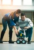 Étudiants de la robotique préparant le robot pour examiner dans l'atelier photo libre de droits