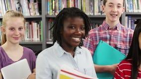 Étudiants de lycée avec des amis dans la bibliothèque clips vidéos