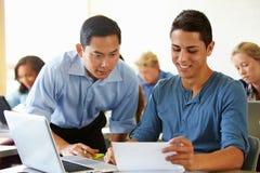 Étudiants de lycée avec des ordinateurs portables d'In Class Using de professeur Photo stock