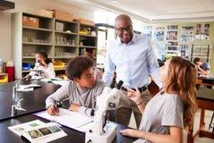 Étudiants de lycée avec le cours de Biologie d'Using Microscope In de tuteur photo libre de droits