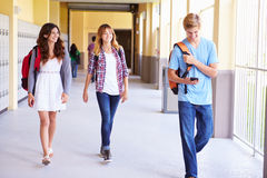 Étudiants de lycée marchant dans le couloir utilisant le téléphone portable Photographie stock libre de droits