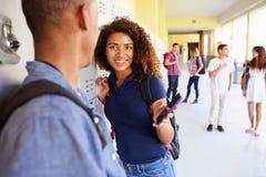 Étudiants de lycée par des casiers regardant le téléphone portable image libre de droits