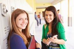 Étudiants de lycée par des casiers regardant le téléphone portable Images stock