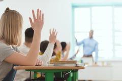 étudiants de lycée soulevant des mains à la réponse photo libre de droits