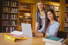 Étudiants de sourire à l'aide de l'ordinateur portable Image libre de droits