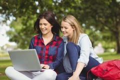 Étudiants de sourire à l'aide de l'ordinateur portable Photos libres de droits