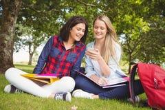 Étudiants de sourire à l'aide du smartphone Photographie stock