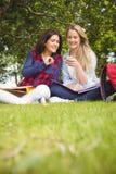 Étudiants de sourire à l'aide du smartphone Photos stock