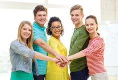 Étudiants de sourire avec des mains sur l'un l'autre Photos libres de droits