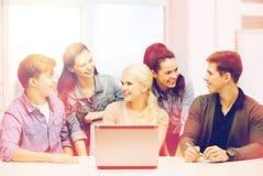 Étudiants de sourire avec l'ordinateur portable à l'école Photo stock