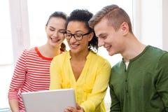 Étudiants de sourire avec le PC de comprimé à l'école Images stock