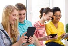 Étudiants de sourire avec le PC de comprimé à l'école Photo libre de droits