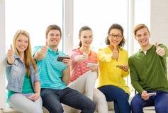 Étudiants de sourire avec le service de mini-messages de smartphone à l'école Image stock