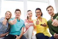 Étudiants de sourire avec le service de mini-messages de smartphone à l'école Photo libre de droits