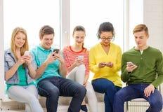 Étudiants de sourire avec le service de mini-messages de smartphone à l'école Image libre de droits