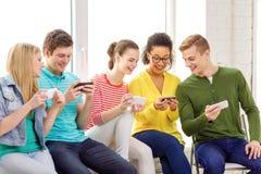Étudiants de sourire avec le service de mini-messages de smartphone à l'école Images libres de droits