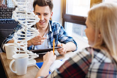 Étudiants de sourire avec plaisir s'asseyant dans le café Photos stock