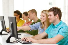 Étudiants de sourire dans la classe d'ordinateur à l'école Photos stock