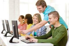 Étudiants de sourire dans la classe d'ordinateur à l'école Photographie stock