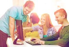 Étudiants de sourire dans la classe d'ordinateur à l'école Image stock