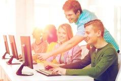 Étudiants de sourire dans la classe d'ordinateur à l'école Photographie stock libre de droits