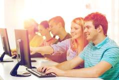 Étudiants de sourire dans la classe d'ordinateur à l'école Photo libre de droits