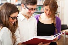 Étudiants de sourire dans une bibliothèque Image libre de droits