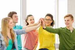 Étudiants de sourire faisant la séance de geste de la haute cinq photo stock